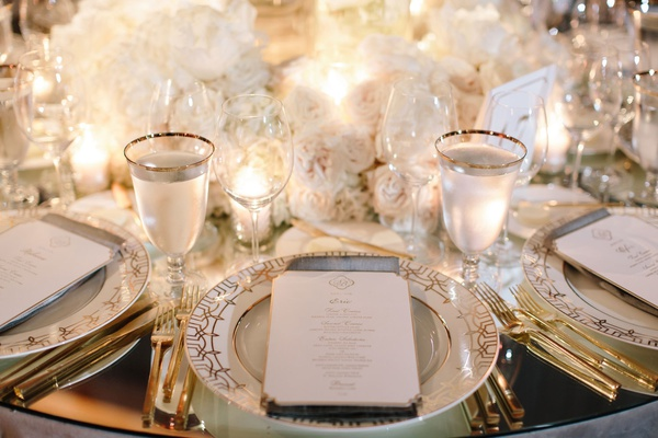 Mirror wedding reception table with white gold china plates gold flatware white roses centerpiece