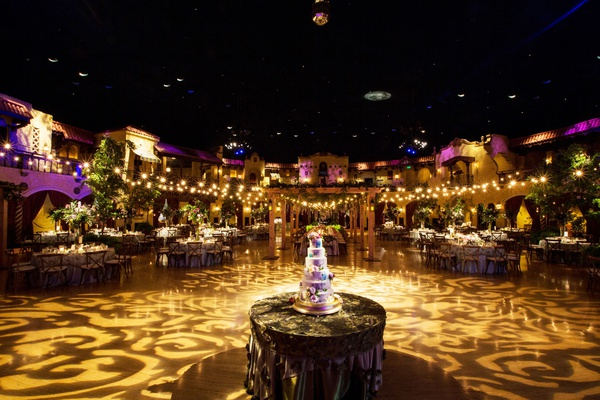 Wedding reception twinkle lights purple lighting tall cake round table gobo light projection