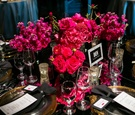 low centerpiece with bright pink hot pink flowers on black table decorations gold plates