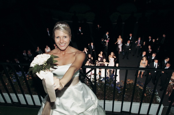 Bride on balcony tossing bridal bouquet