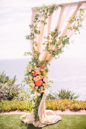 wedding ceremony overlooking ocean drapery arch pink orange yellow flowers