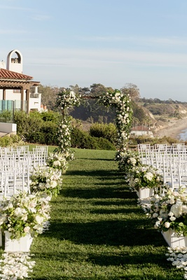 Wedding ceremony green grass urns boxes filled with flowers greenery white chairs bacara ocean view