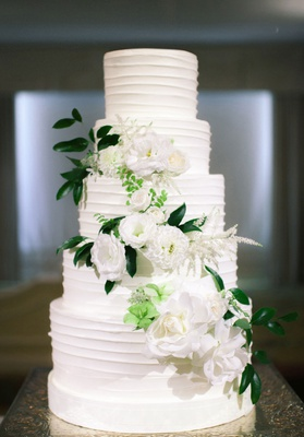 crisp white wedding cake with fresh flowers down the tiers