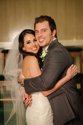 Man in grey suit and woman in wedding dress hugging