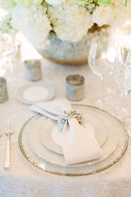 Clear charger plate with white napkin and white and silver napkin ring at wedding reception