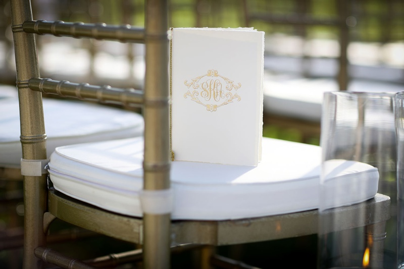 wedding ceremony program gold monogram booklet on white chair cushion gold chair