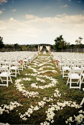 White ceremony chairs and petal-covered aisle