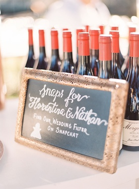Wine bottles with red tops and frame with chalkboard calligraphy sign snapchat geofilter