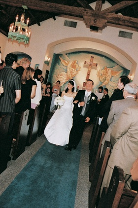 Bride and groom walk up aisle after saying I do