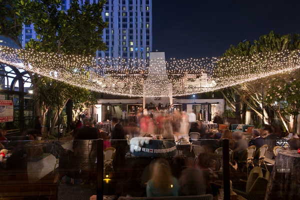wedding guests at outdoor reception lounge area just married settee twinkle light canopy downtown la