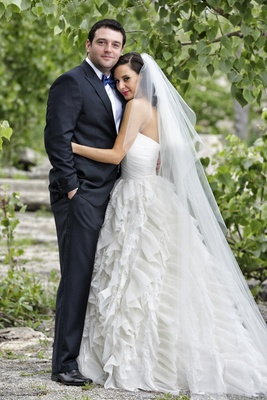 Bride in ruffle wedding dress with groom in tuxedo