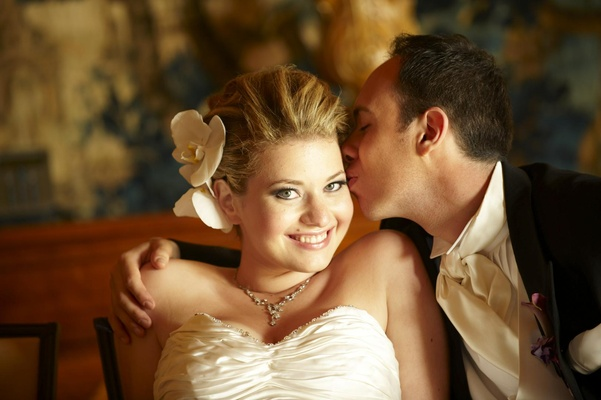 Groom kissing bride on cheek with orchid hair accessory