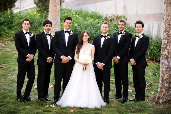 Bride in Sabrina Dahan a line wedding dress with groomsmen in black suits and bow ties