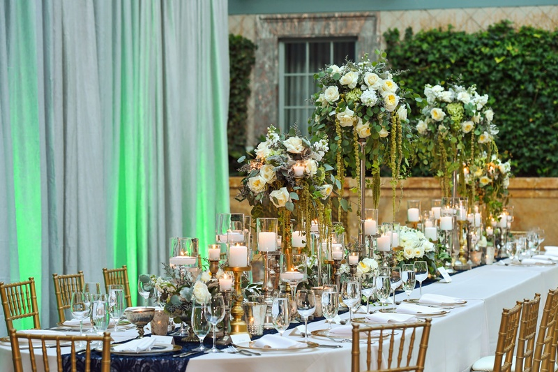wedding reception table white linen gold chair high low centerpiece greenery white rose navy runner