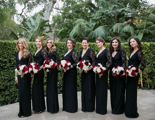 Bridesmaids in black long sleeve v-neck lace bridesmaid dresses carrying red and white bouquets