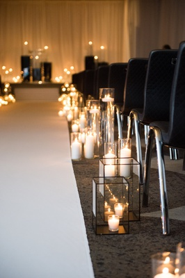 candles in hurricanes and glass boxes along wedding aisle
