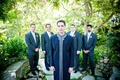Groom in a navy sherwani with a silver trim and groomsmen in dark suits