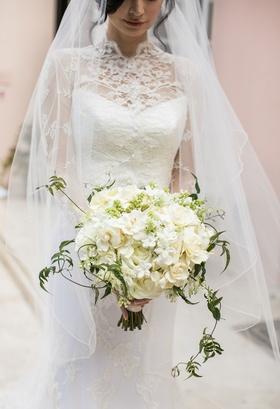 Bride holding ivory bouquet composed of roses, gardenias, stephanotis blossoms, green vines