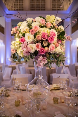 Wedding reception table with blush & ivory roses, hydrangeas, orchids, greenery in clear vase