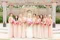 bride in strapless wedding dress big pink bouquet bridesmaids in long v neck dresses in pale pink