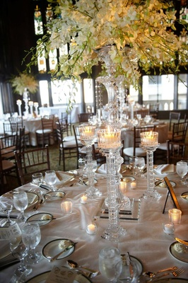 Wedding reception table with tall crystal candle holders and vase with white flowers