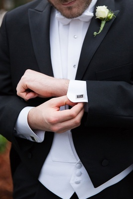Groom adjusting cuff links with monogram cufflink cufflinks white vest and bow tie rose boutonniere