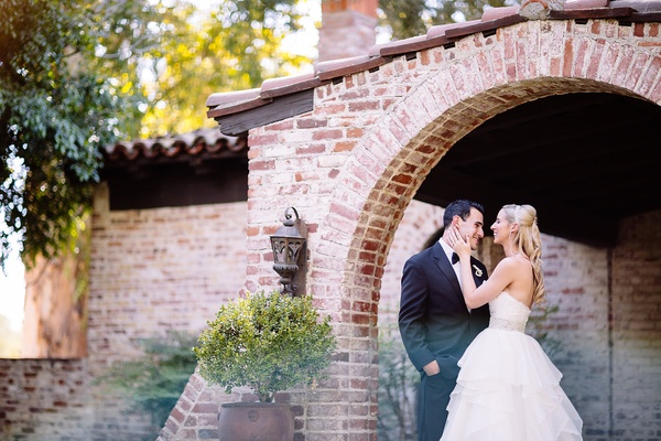 Bride in a strapless Hayley Paige dress with tiered skirt, beaded belt laughs with groom