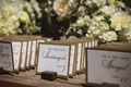 Outdoor ranch wedding reception with place cards with burlap print edges propped on tiny wood blocks