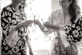 Black and white photo of bride in robe cheers sipping champagne in flutes with bridesmaids in robe