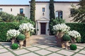 Boxwood spheres and urns filled with white flowers at Villa Sevillano