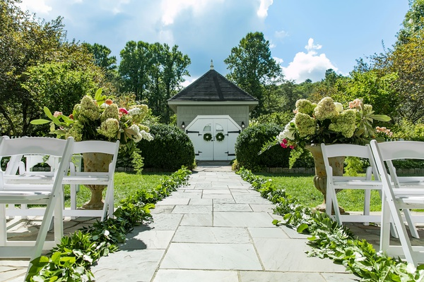 wedding ceremony outdoor old edwards inn stone aisle greenery white chairs urn with colorful flowers