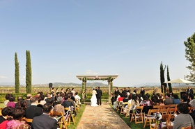 Bride and groom at altar in front of vineyard