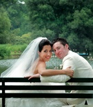 Couple on park bench in front of pond with a number of goose
