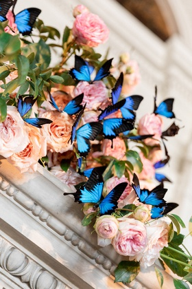 mantle decorated with pink and peach roses with blue Papillio Ulysses butterflies