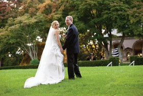Bride and groom look back at camera in grass