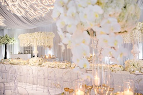Wedding reception white long table clear chairs monogram orchids drapery projection lighting design