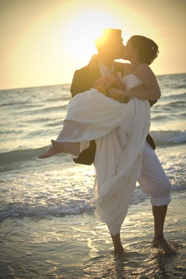 Bride and groom sharing a beachside sunset kiss