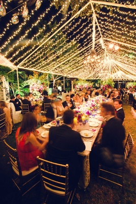 Wedding reception guests at long family table under tent lined with string lights