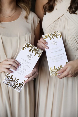 attendants in champagne dresses holding white and gold foil ceremony programs rectangle design