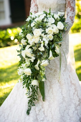 Bride in Isabelle Armstrong wedding dress holding cascading bouquet of green leaves, white flowers