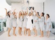 Bride in white robe and bridesmaids in pale gray grey blue robes tossing confetti