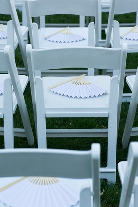 Light purple wooden fans on white ceremony chairs
