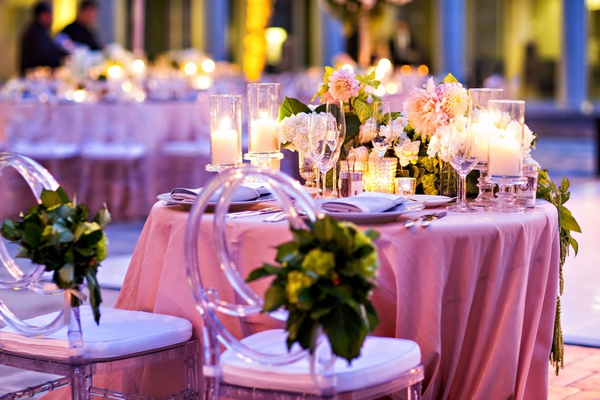 Sweetheart table round with clear back chairs Lucite and candles low flower arrangements dahlias