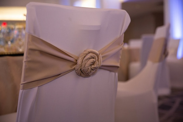 Wedding reception with chairs in white sleeves, and golden fabric rosette