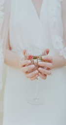 Bride holding wine goblet of water with fresh rose