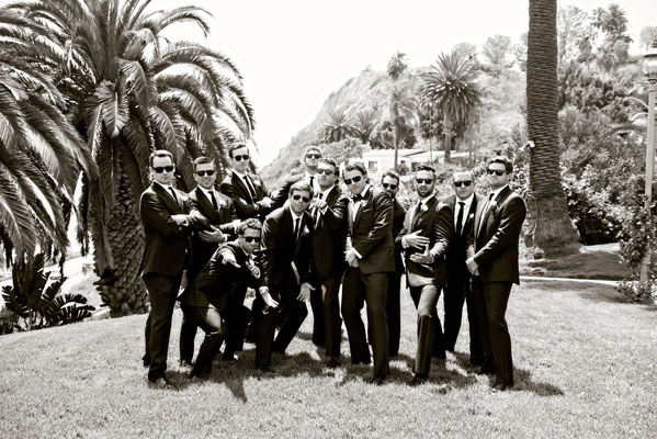 Black and white photo of groom and groomsmen in sunglasses on lawn at bel air bay club palm trees
