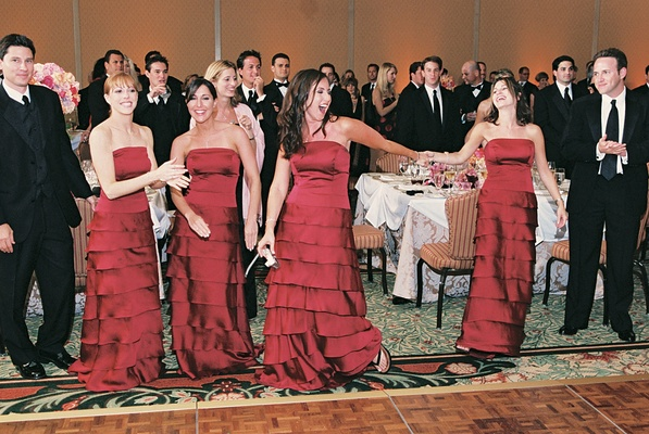 bridesmaids wearing red dresses sing at reception