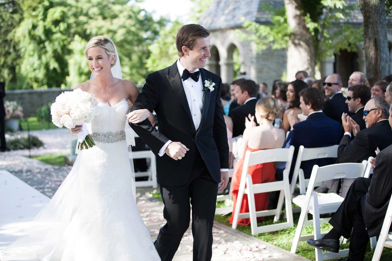 happy newlyweds walk back up the aisle after their outdoor ceremony