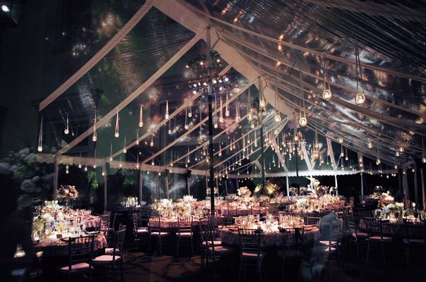 Candlelit dinner service under clear tent