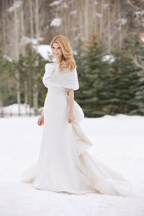 Bride wearing ivory wedding dress and fur shawl